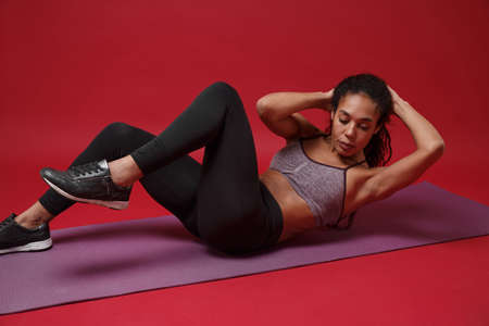 Strong young african american woman in sportswear posing working out isolated on red background in studio. Sport exercises healthy lifestyle concept. Sitting on fitness mat, doing abdominal exercises. Reklamní fotografie