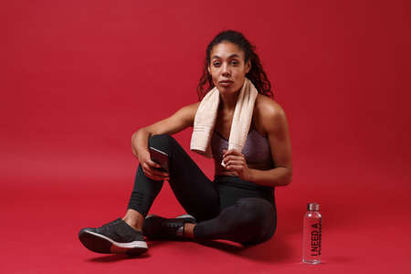 Attractive young african american woman in sportswear working out isolated on red background. Sport exercises healthy lifestyle concept. Sit with towel over her neck, water bottle, using mobile phone.