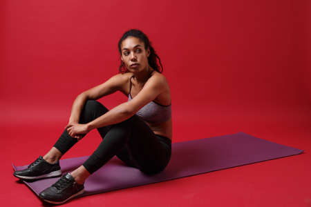 Beautiful young african american woman in sportswear posing working out isolated on red background studio portrait. Sport exercises healthy lifestyle concept. Sitting on fitness mat, looking aside.