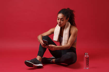 Smiling young african american woman in sportswear working out isolated on red background. Sport exercises healthy lifestyle concept. Sit with towel over her neck, water bottle, using mobile phone.