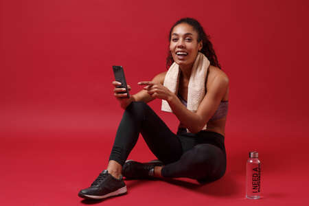 Cheerful young african american woman in sportswear isolated on red background. Sport exercises healthy lifestyle concept. Sit with towel over neck water bottle, pointing index finger on mobile phone.