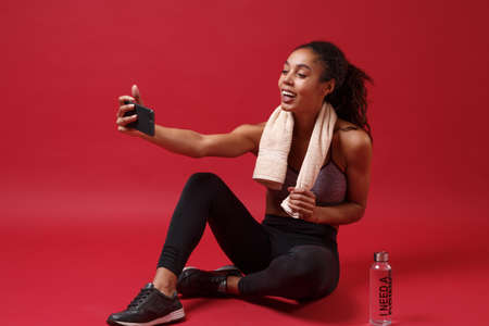Cheerful african american woman in sportswear working out isolated on red background. Sport exercises healthy concept. Sitting with towel over her neck water bottle, doing selfie shot on mobile phone. Reklamní fotografie
