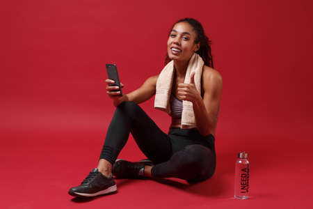 Funny young african american woman in sportswear isolated on red background. Sport exercises healthy lifestyle concept. Sit with towel over her neck water bottle, using mobile phone, showing thumb up.