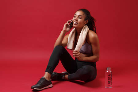 Smiling african american woman in sportswear working out isolated on red background. Sport exercises healthy lifestyle concept. Sit with towel over her neck, water bottle, talking on mobile phone. Reklamní fotografie