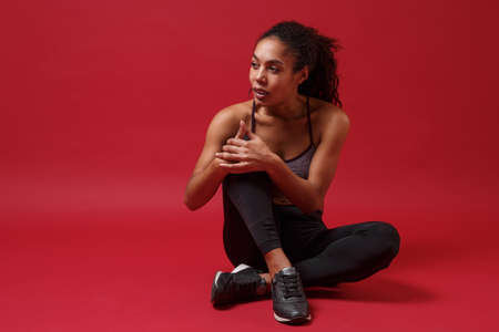 Attractive young african american sports fitness woman in sportswear posing working out isolated on red background studio portrait. Sport exercises healthy lifestyle concept. Sitting, looking aside. Reklamní fotografie
