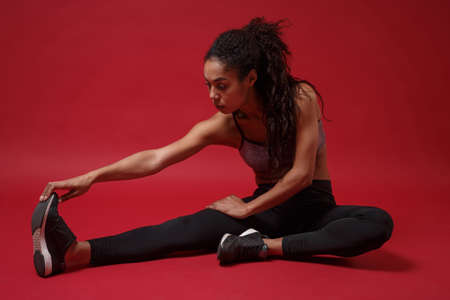 Beautiful young african american woman in sportswear posing working out isolated on red background studio portrait. Sport exercises healthy lifestyle concept. Sitting, doing stretching exercising.