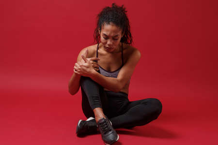 Displeased young african american sports fitness woman in sportswear posing working out isolated on red background studio portrait. Sport exercises healthy lifestyle concept. Sitting, touching knee. Reklamní fotografie