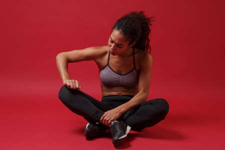 Concerned young african american sports fitness woman in sportswear posing working out isolated on red background studio portrait. Sport exercises healthy lifestyle concept. Sitting, touching knee.