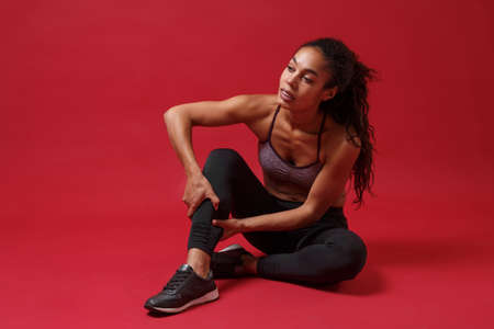 Beautiful young african american sports fitness woman in sportswear posing working out isolated on red background. Sport exercises healthy lifestyle concept. Sitting, touching ankle, looking aside.