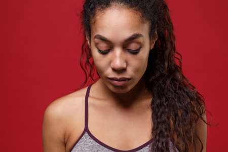 Close up of young african american sports fitness woman in sportswear posing working out isolated on red wall background studio portrait. Sport exercises healthy lifestyle concept. Looking down.