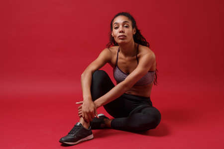 Young african american sports fitness woman in sportswear posing working out isolated on red wall background studio portrait. Sport exercises healthy lifestyle concept. Sitting, looking camera.