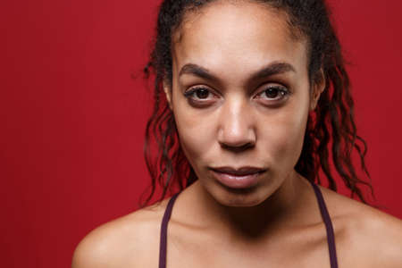 Close up of young african american sports fitness woman in sportswear posing working out isolated on red wall background studio portrait. Sport exercises healthy lifestyle concept. Looking camera. Reklamní fotografie