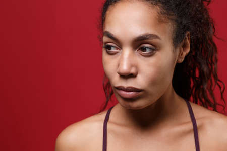 Close up of young african american sports fitness woman in sportswear posing working out isolated on red wall background studio portrait. Sport exercises healthy lifestyle concept. Looking aside.