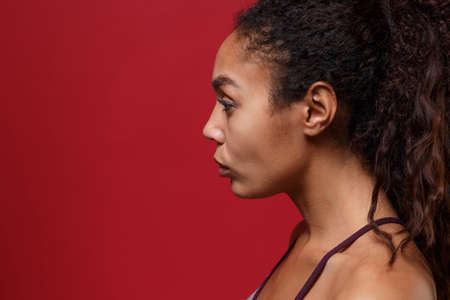 Side view of young african american sports fitness woman in sportswear posing working out isolated on red wall background studio portrait. Sport exercises healthy lifestyle concept. Looking aside. Reklamní fotografie