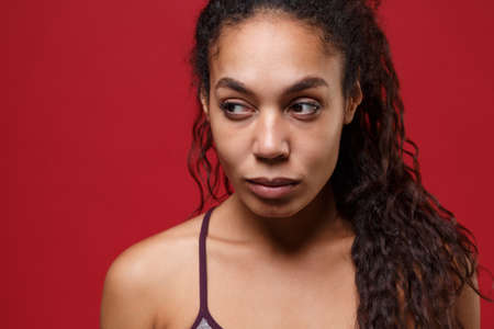 Beautiful young african american sports fitness woman in sportswear posing working out isolated on red wall background studio portrait. Sport exercises healthy lifestyle concept. Looking aside. Reklamní fotografie