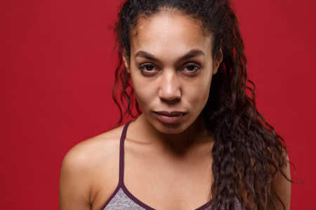 Confident young african american sports fitness woman in sportswear posing working out isolated on red wall background studio portrait. Sport exercises healthy lifestyle concept. Looking camera.