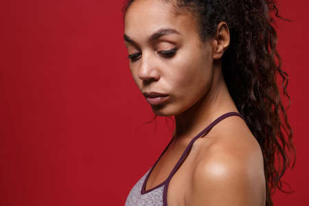 Side view of young african american sports fitness woman in sportswear posing working out isolated on red wall background studio portrait. Sport exercises healthy lifestyle concept. Looking down.