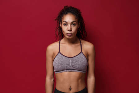 Attractive young african american sports fitness woman in sportswear posing working out isolated on red wall background studio portrait. Sport exercises healthy lifestyle concept. Looking camera.