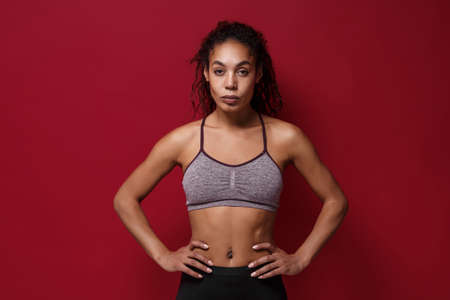 Beautiful young african american sports fitness woman in sportswear posing working out isolated on red wall background. Sport exercises healthy lifestyle concept. Standing with arms akimbo on waist. Reklamní fotografie