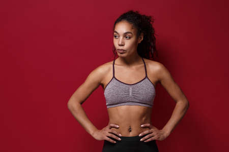 Young african american sports fitness woman in sportswear posing working out isolated on red background. Sport exercises healthy lifestyle concept. Standing with arms akimbo on waist, looking aside. Reklamní fotografie