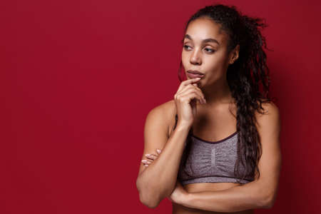 Pensive young african american sports fitness woman in sportswear posing working out isolated on red wall background. Sport exercises healthy lifestyle concept. Put hand prop up on chin looking aside.
