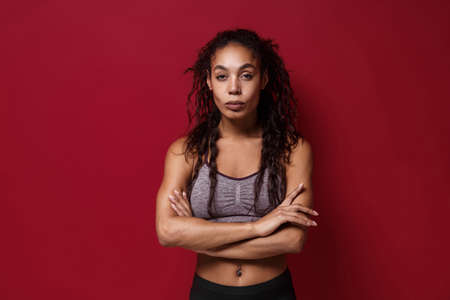 Stunning young african american sports fitness woman in sportswear posing working out isolated on red wall background studio portrait. Sport exercises healthy lifestyle concept. Holding hands crossed.