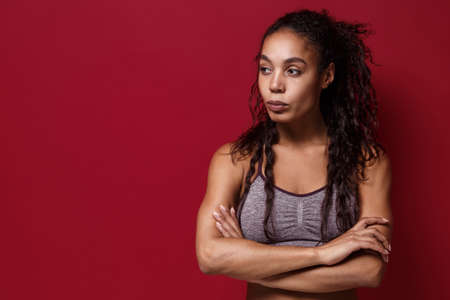 Beautiful young african american sports fitness woman in sportswear posing working out isolated on red wall background. Sport exercises healthy lifestyle concept. Holding hands crossed, looking aside. Reklamní fotografie