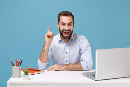 Excited man in light shirt sit work at desk with pc laptop isolated on blue background. Achievement business career lifestyle concept. Mock up copy space. Holding index finger up with great new idea.