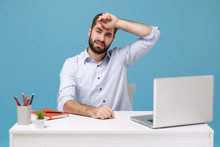 Exhausted tired young bearded man in light shirt sit work at desk with pc laptop isolated on pastel blue background. Achievement business career lifestyle concept. Mock up copy space Put hand on head.