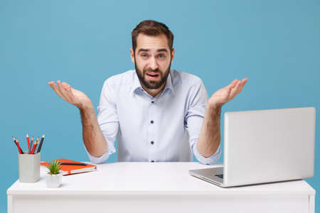 Perplexed young bearded man in light shirt sit and work at desk with pc laptop isolated on pastel blue background. Achievement business career lifestyle concept. Mock up copy space. Spreading hands.