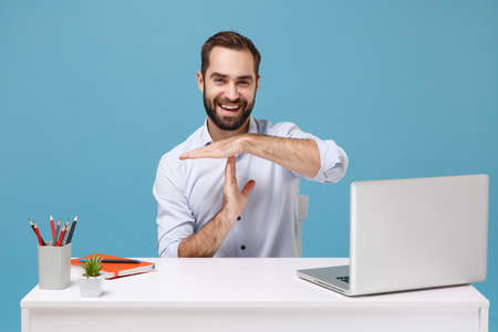 Cheerful young man in light shirt sit and work at desk with pc laptop isolated on pastel blue background. Achievement business career lifestyle concept. Mock up copy space. Hold hands perpendicularly.