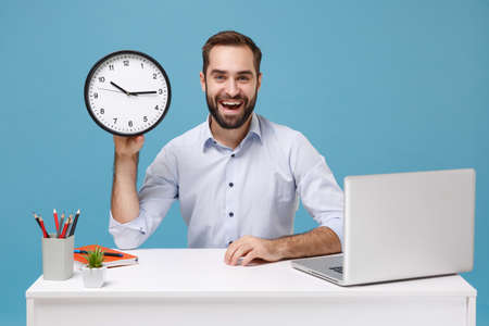Cheerful young bearded man in light shirt sit and work at white desk with pc laptop isolated on pastel blue background in studio. Achievement business career concept. Mock up copy space. Hold clock.