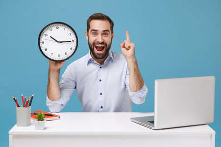 Amazed young man in shirt work at desk with pc laptop isolated on pastel blue background. Achievement business career concept. Mock up copy space. Hold clock point index finger up with great new idea. 版權商用圖片