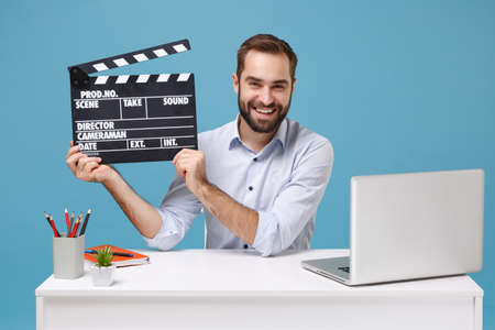 Smiling young man in light shirt work at desk with pc laptop isolated on pastel blue background. Achievement business career concept. Mock up copy space. Hold classic black film making clapperboard.