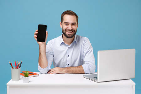 Smiling young man in light shirt sit work at desk with pc laptop isolated on pastel blue background. Achievement business career concept. Mock up copy space. Hold mobile phone with blank empty screen.