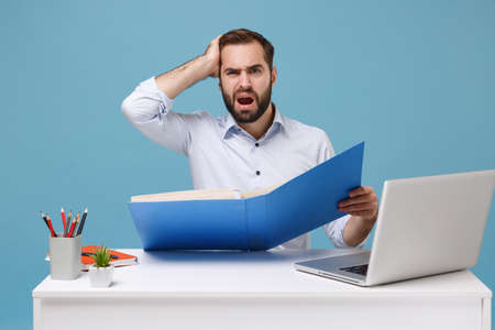 Perplexed young bearded man in light shirt sit work at desk with pc laptop isolated on pastel blue background. Achievement business career concept. Mock up copy space. Hold folder for papers document.