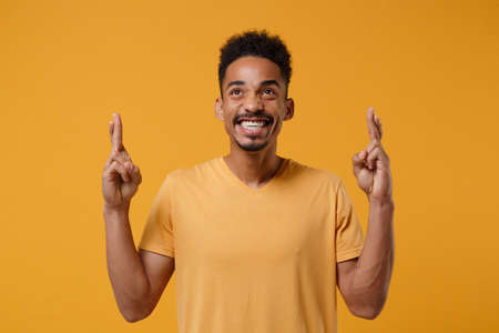 Young african american guy in casual t-shirt posing isolated on yellow orange background. People lifestyle concept. Mock up copy space. Waiting for special moment keeping fingers crossed, making wish.