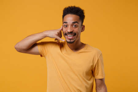 Funny young african american guy in casual t-shirt posing isolated on yellow orange wall background in studio. People lifestyle concept. Mock up copy space. Doing phone gesture like says call me back.