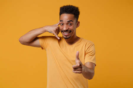 Smiling young african american guy posing isolated on yellow orange background. People lifestyle concept. Mock up copy space. Doing phone gesture like says call me back, point index finger on camera.
