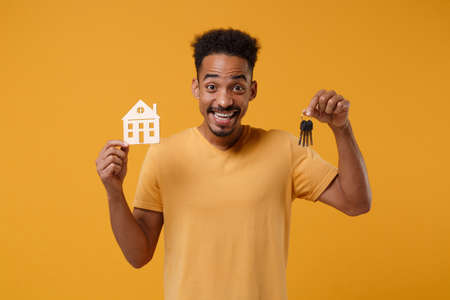 Excited young african american guy in casual t-shirt posing isolated on yellow orange background, studio portrait. People lifestyle concept. Mock up copy space. Hold in hands house and bunch of keys. Stock Photo