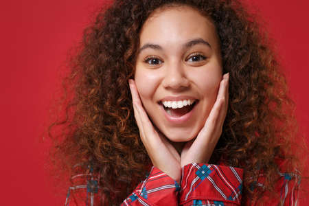 Close up of funny young african american girl in pajamas homewear posing while resting at home isolated on red background. Relax good mood lifestyle concept. Mock up copy space. Put hands on cheeks.