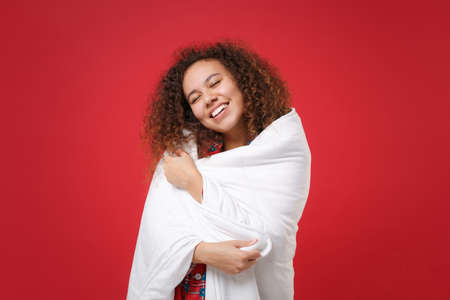 Smiling young african american girl in pajamas homewear posing while resting at home isolated on red background. Relax good mood lifestyle concept. Mock up copy space. Sleeping wrapping in blanket.