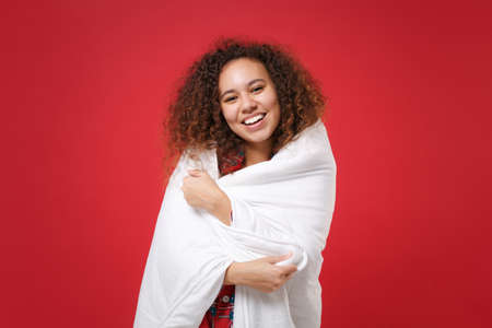 Cheerful young african american girl in pajamas homewear posing while resting at home isolated on red background in studio. Relax good mood lifestyle concept. Mock up copy space. Wrapping in blanket.