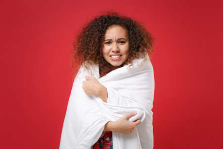 Dissatisfied young african american girl in pajamas homewear posing while resting at home isolated on red wall background. Relax good mood lifestyle concept. Mock up copy space. Wrapping in blanket.