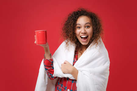 Excited young african american girl in pajamas homewear rest at home isolated on red background. Relax good mood lifestyle concept. Mock up copy space. Wrapping in blanket hold cup of coffee or tea.