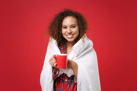 Smiling young african american girl in pajamas homewear rest at home isolated on red background. Relax good mood lifestyle concept. Mock up copy space. Wrapping in blanket, hold cup of coffee or tea.