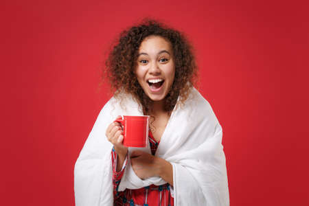 Surprised young african american girl in pajamas homewear rest at home isolated on red background. Relax good mood lifestyle concept. Mock up copy space. Wrapping in blanket hold cup of coffee or tea.