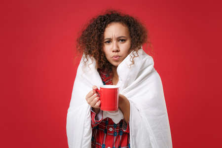 Worried young african american girl in pajamas homewear rest at home isolated on red background. Relax good mood lifestyle concept. Mock up copy space. Wrapping in blanket, hold cup of coffee or tea.