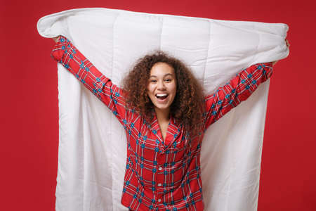Laughing funny young african american girl in pajamas homewear posing while resting at home isolated on red background in studio. Relax good mood lifestyle concept. Mock up copy space. Hold blanket. Imagens