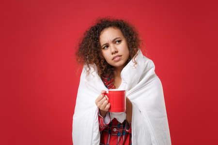 Displeased african american girl in pajamas homewear resting at home isolated on red background. Relax good mood lifestyle concept. Mock up copy space. Wrapping in blanket, hold cup of coffee or tea.